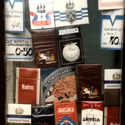 "15.	Cigarettes in a kiosk. Turgenev Square, Sadovaya. Leningrad. 1983. Note in the centre the blue packet of Belomor Canal ""White Sea Canal"" (ВЕЛОМОРКАНАЛ) cigarettes. The White Sea canal was built in the 1930s using unpaid prison labour. the cigarettes commemorated this event throughout the Soviet period"