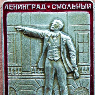 47.	Lenin lapel badge depicting Lenin statue in front of the Smolny Institute in Leningrad. The Smolny was the headquarters of the Bolsheviks during the October 1917 uprising.